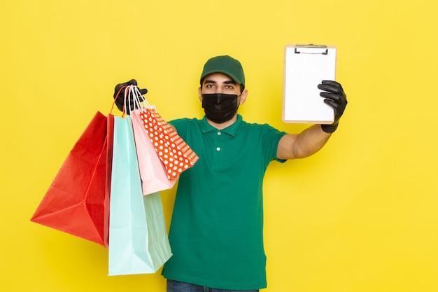 Вид спереди молодой мужчина-курьер в зеленой рубашке с зеленой кепкой держит блокнот и пакеты с покупками на желтом