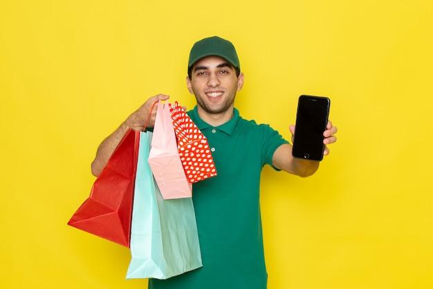 Вид спереди молодой мужчина-курьер в зеленой рубашке с зеленой кепкой держит телефон и пакеты с покупками на желтом