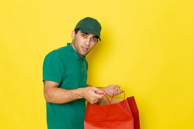 Вид спереди молодой курьер-мужчина в зеленой рубашке с зеленой кепкой, держащий красный пакет покупок на желтом