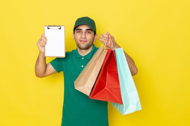 Вид спереди молодой мужчина-курьер в зеленой рубашке с зеленой кепкой, держащий пакеты с покупками и блокнот на желтом