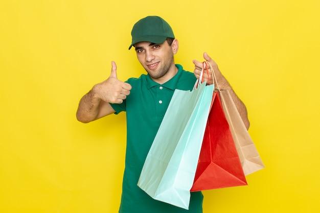Вид спереди молодой курьер-мужчина в зеленой рубашке с зеленой кепкой держит пакеты с покупками и показывает удивительный знак