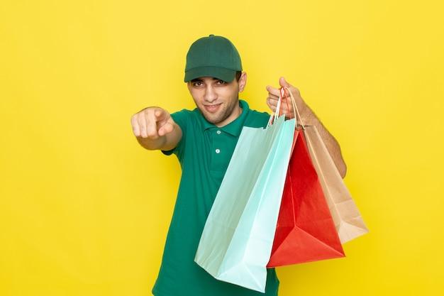 黄色の笑顔でショッピングパッケージを保持している緑のシャツグリーンキャップの正面の若い男性宅配便