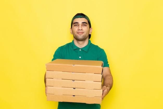 笑顔とサービスの色を提供する黄色の背景に配信ボックスを保持している緑のシャツグリーンキャップの正面の若い男性宅配便