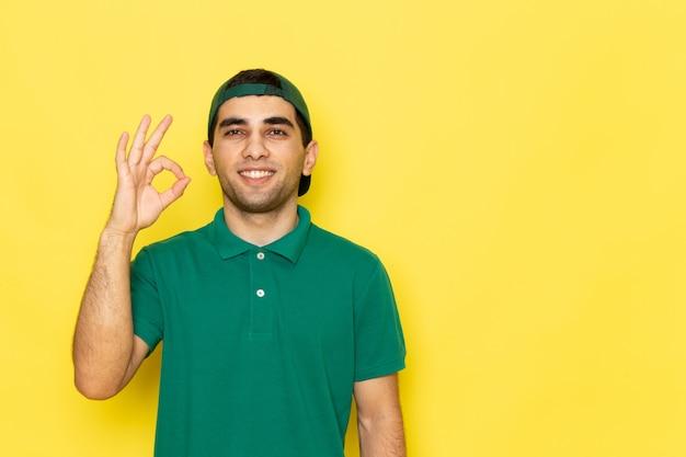 正面から見た緑のシャツの緑の帽子の若い男性宅配便笑顔とサービスの色を提供する黄色の背景の仕事に笑顔でいいサインを示す
