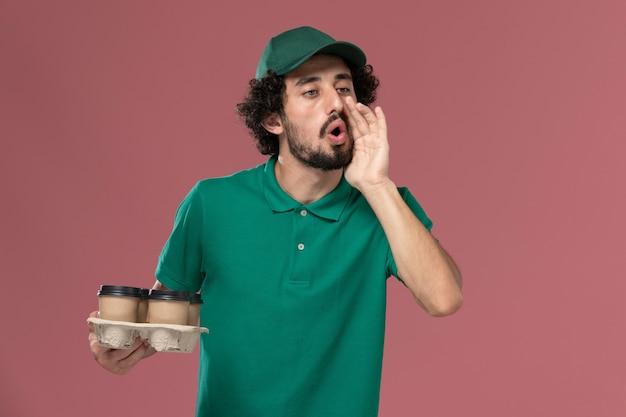 正面図緑の制服とケープを保持している若い男性の宅配便茶色の配達コーヒーカップを保持しているライトピンクの背景サービス制服配達労働者の仕事で誰かを呼び出す