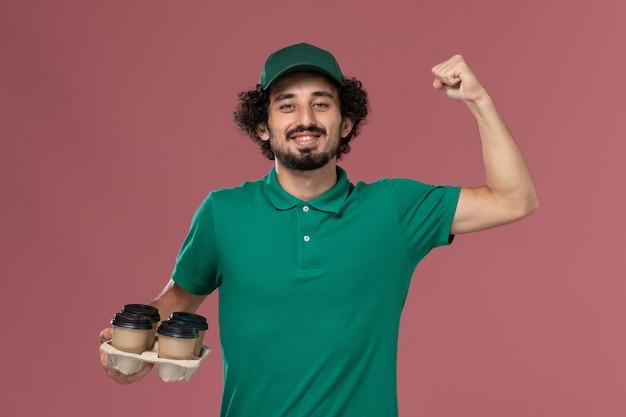 緑のユニフォームと薄ピンクの背景サービスの制服配達労働者の仕事で曲がる茶色の配達コーヒーカップを保持している岬の正面図若い男性の宅配便