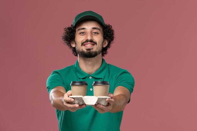 緑の制服とピンクの背景に茶色の配達コーヒーカップを保持している岬の正面図若い男性の宅配便サービス仕事制服配達労働者
