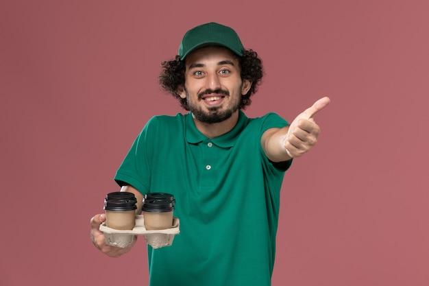 緑の制服と薄ピンクの背景サービス制服配達の仕事で茶色の配達コーヒーカップを保持している岬の正面図若い男性の宅配便