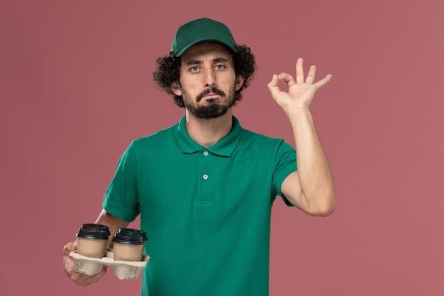 緑の制服と薄ピンクの背景に茶色の配達コーヒーカップを保持している岬の正面図若い男性の宅配便制服配達労働者の仕事