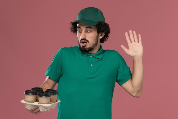 緑の制服と薄ピンクの背景サービス制服配達労働者に茶色の配達コーヒーカップを保持している岬の正面図若い男性宅配便