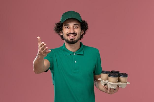 緑の制服とピンクの背景に茶色の配達コーヒーカップを保持している岬の正面図若い男性の宅配便制服配達仕事の男性
