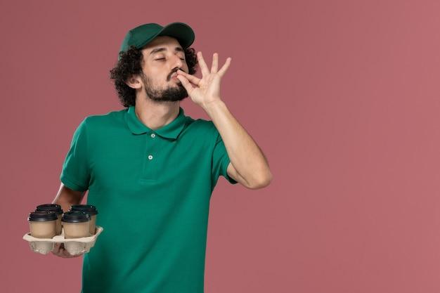 緑の制服とピンクの背景に茶色の配達コーヒーカップを保持している岬の正面図若い男性の宅配便制服配達仕事の仕事