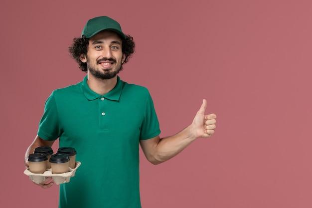 ピンクの背景サービス制服配達労働者に茶色の配達コーヒーカップを保持している緑の制服と岬の正面図若い男性宅配便