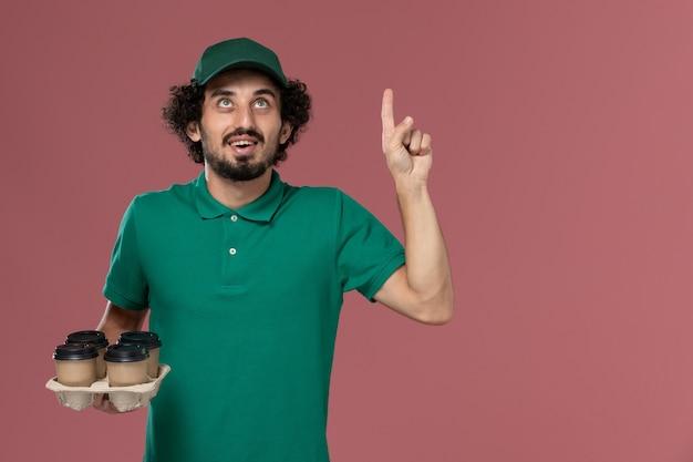 緑の制服とピンクの背景サービス制服配達労働者の仕事でポーズをとって考えている茶色の配達コーヒーカップを保持している岬の正面図若い男性宅配便