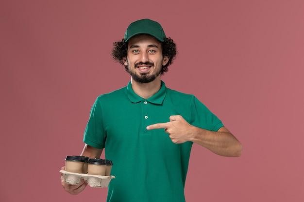 緑のユニフォームと薄ピンクの背景に微笑んでいる茶色の配達コーヒーカップを保持している岬の正面図若い男性の宅配便制服配達労働者の仕事