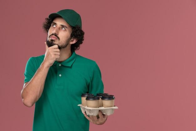 緑のユニフォームと薄ピンクの背景サービスの制服配達の仕事の仕事を考えて茶色の配達コーヒーカップを保持している岬の正面図若い男性の宅配便