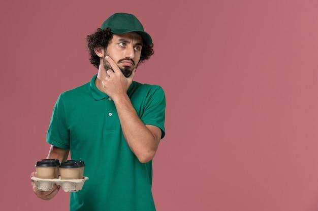正面図緑の制服とケープを保持している茶色の配達コーヒーカップの若い男性の宅配便ピンクの背景サービス制服配達労働者の仕事