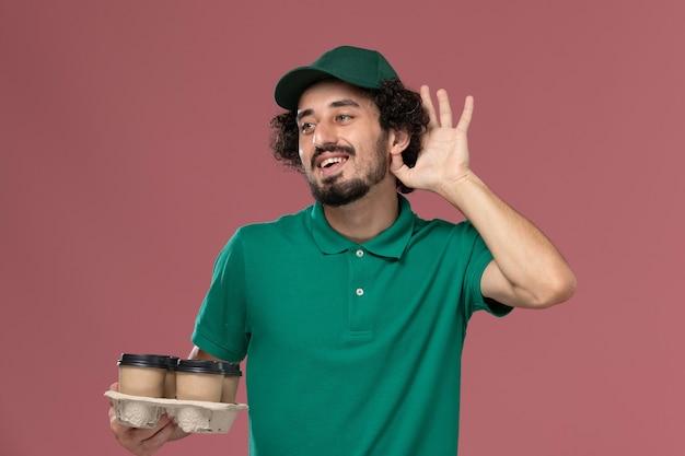 緑の制服とケープを持った若い男性の宅配便の正面図明るいピンクの背景サービスの制服配達労働者の仕事で聞いてみようとしている茶色の配達コーヒーカップを保持しています