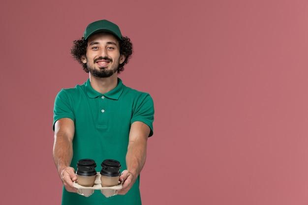 正面図緑の制服とピンクの背景サービスジョブ制服配達労働者に笑顔で茶色の配達コーヒーカップを保持している岬の若い男性宅配便