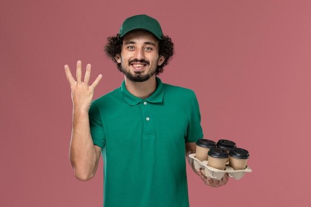 緑の制服とピンクの背景に笑顔で茶色の配達コーヒーカップを保持している岬の正面図若い男性宅配便制服配達仕事の男性
