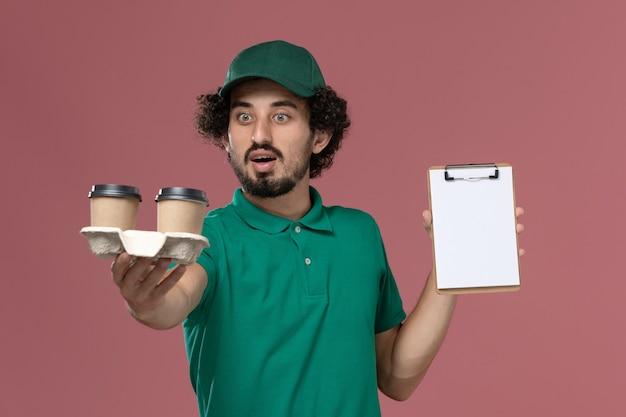 緑のユニフォームと薄ピンクの背景サービスジョブユニフォーム配達の配達コーヒーカップとメモ帳を保持している岬の正面図若い男性宅配便
