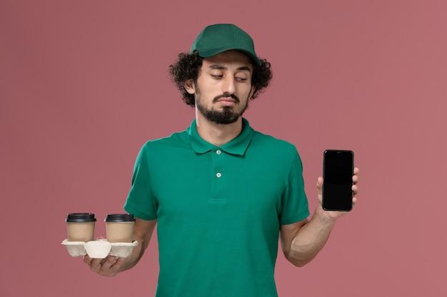 正面図緑の制服を着た若い男性の宅配便と淡いピンクの背景に配達コーヒーカップと電話を保持している岬サービス仕事制服配達