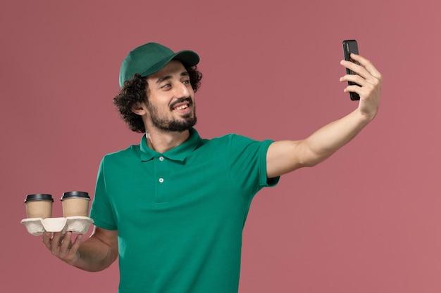 녹색 유니폼과 케이프 핑크 배경 서비스 작업 유니폼 배달 노동자에 사진을 복용 배달 커피 컵을 들고 전면보기 젊은 남성 택배