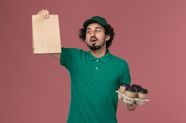 緑のユニフォームと薄ピンクの背景サービスの均一な配達の仕事で食品パッケージと配達コーヒーカップを保持している岬の正面図若い男性の宅配便