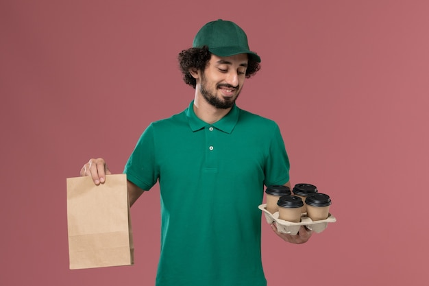 ピンクの背景サービスの制服配達の仕事で食品パッケージと配達コーヒーカップを保持している緑の制服と岬の正面図若い男性の宅配便
