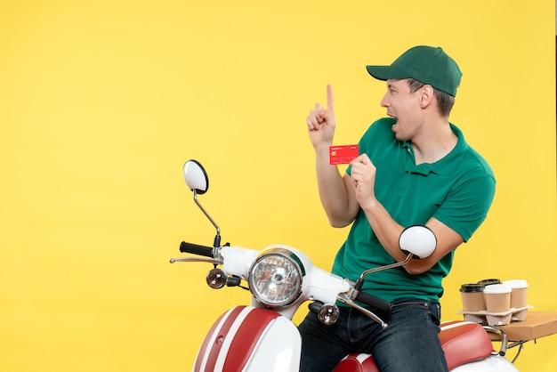 노란색에 은행 카드를 들고 녹색 제복을 입은 전면보기 젊은 남성 택배