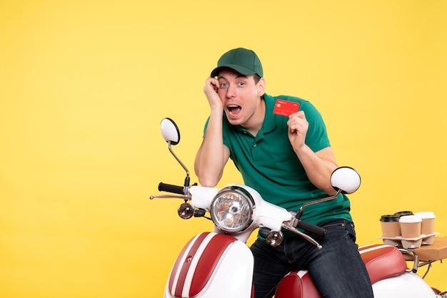 黄色の銀行カードを保持している緑の制服を着た正面の若い男性宅配便