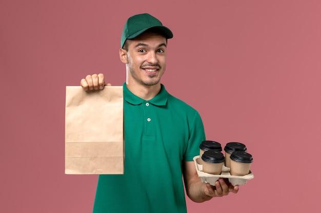 ピンクの机の上に茶色のコーヒーカップと食品パッケージを保持している緑の制服を着た若い男性の宅配便の正面図