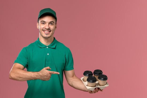 明るいピンクの背景に笑みを浮かべてコーヒーカップを保持している緑の制服を着た若い男性宅配便の正面図