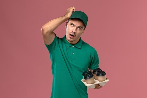ピンクの背景を考えてコーヒーカップを保持している緑の制服を着た若い男性宅配便の正面図