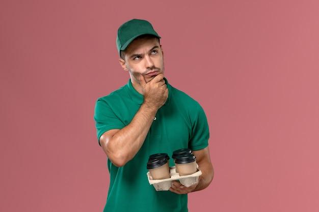 ピンクの机の上に思考表現とコーヒーカップを保持している緑の制服を着た若い男性宅配便の正面図