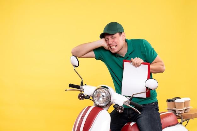 Вид спереди молодой курьер-мужчина в зеленой форме держит заметку на желтом