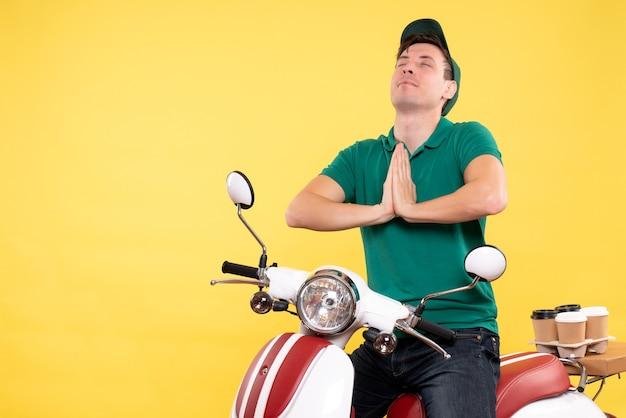 黄色いバイクに緑の制服を着た正面の若い男性宅配便