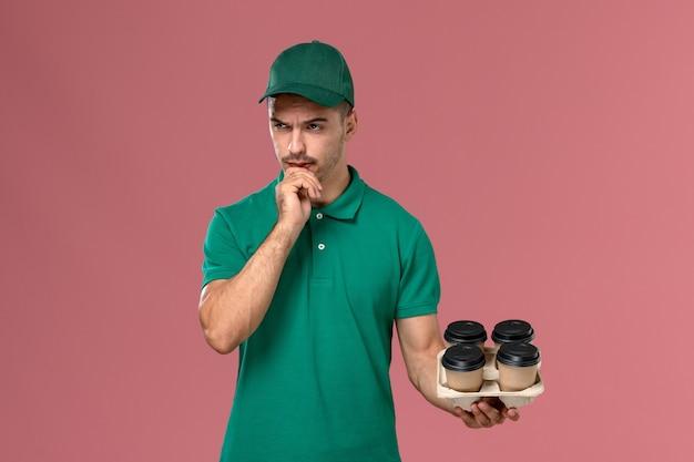 正面図緑の制服を着た若い男性の宅配便ピンクの背景に茶色のコーヒーカップを考えて保持します。