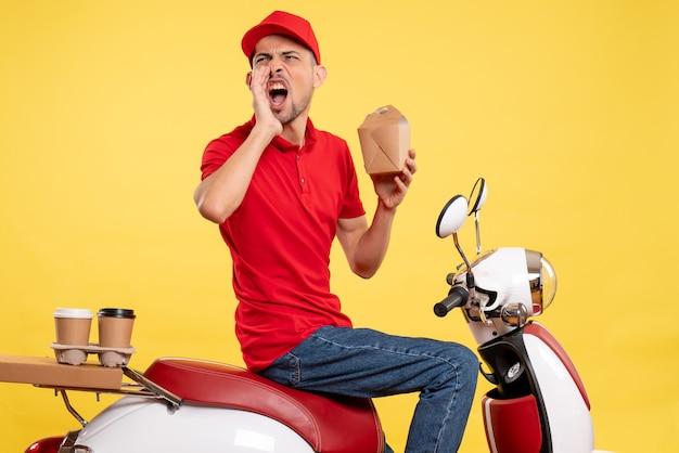 Вид спереди молодой курьер-мужчина в красной форме громко звонит на желтом фоне