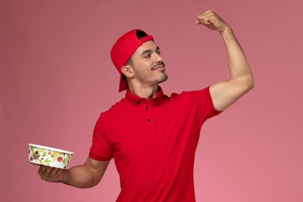 淡いピンクの背景に配達ボウルを曲げて保持している赤い制服ケープの正面図若い男性宅配便。