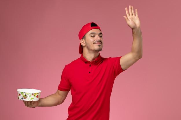 配達ボウルを保持し、淡いピンクの背景に手を振って赤い制服ケープの正面図若い男性宅配便。