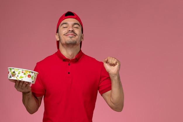 明るいピンクの背景に配達ボウルを保持している赤い制服ケープの正面図若い男性宅配便。