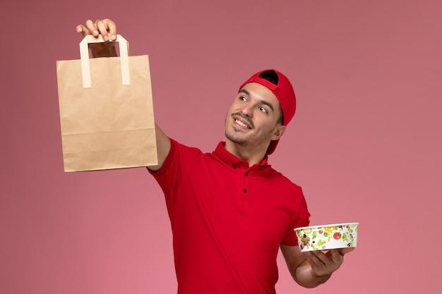 ピンクの背景に食品パッケージとボウルを保持している赤い制服の岬の正面図若い男性宅配便。