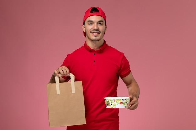 ピンクの背景に笑顔で食品パッケージとボウルを保持している赤い制服の岬の正面図若い男性宅配便。