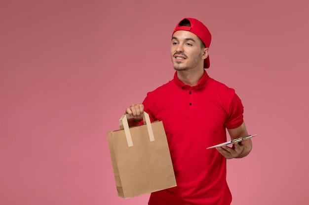 淡いピンクの背景に食品パッケージとメモ帳を保持している赤い制服の岬の正面図の若い男性の宅配便。