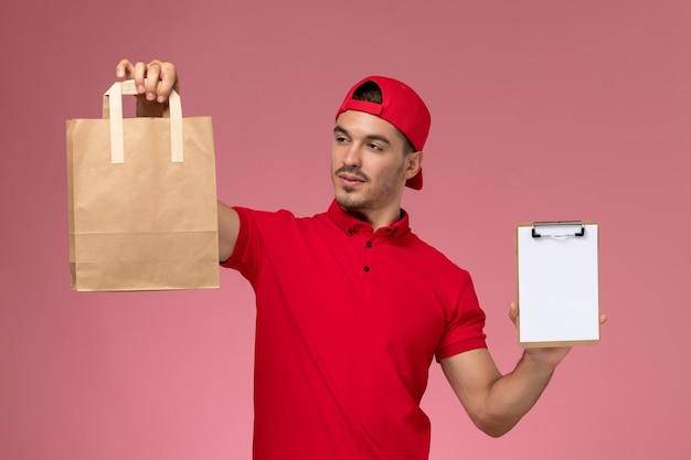 ピンクの背景に食品パッケージとメモ帳を保持している赤い制服の岬の正面図若い男性宅配便。