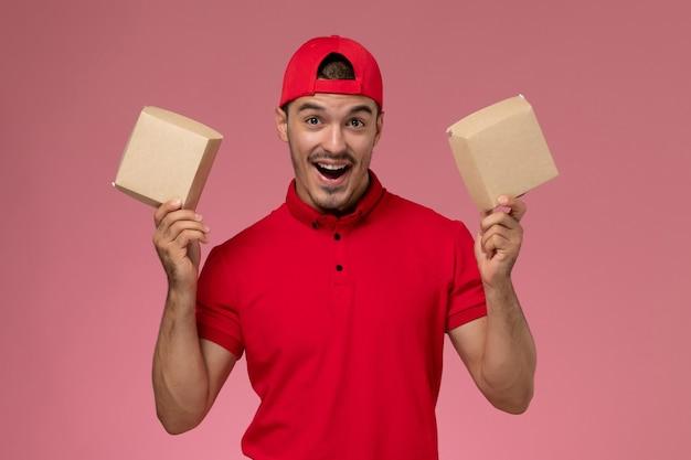 ピンクの背景に食べ物と小さなパッケージを保持している赤い制服の岬の正面図若い男性宅配便。