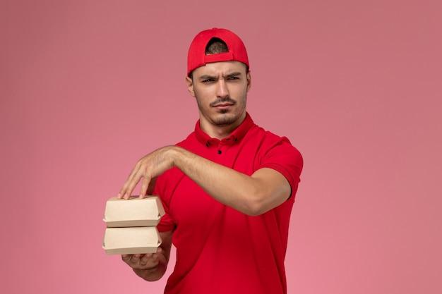 淡いピンクの背景に食べ物と小さなパッケージを保持している赤い制服の岬の正面図の若い男性の宅配便。