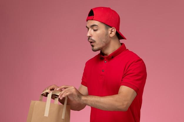紙の食品パッケージを保持し、ピンクの背景でそれを確認する赤い制服ケープの正面図若い男性宅配便。