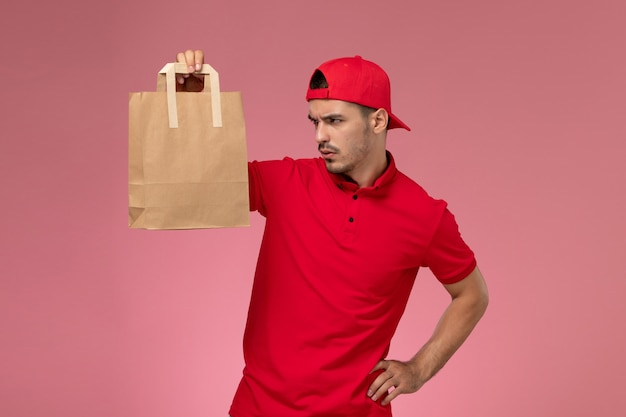 ピンクの机の上に紙の食品パッケージを保持している赤い制服の岬の正面図の若い男性の宅配便。